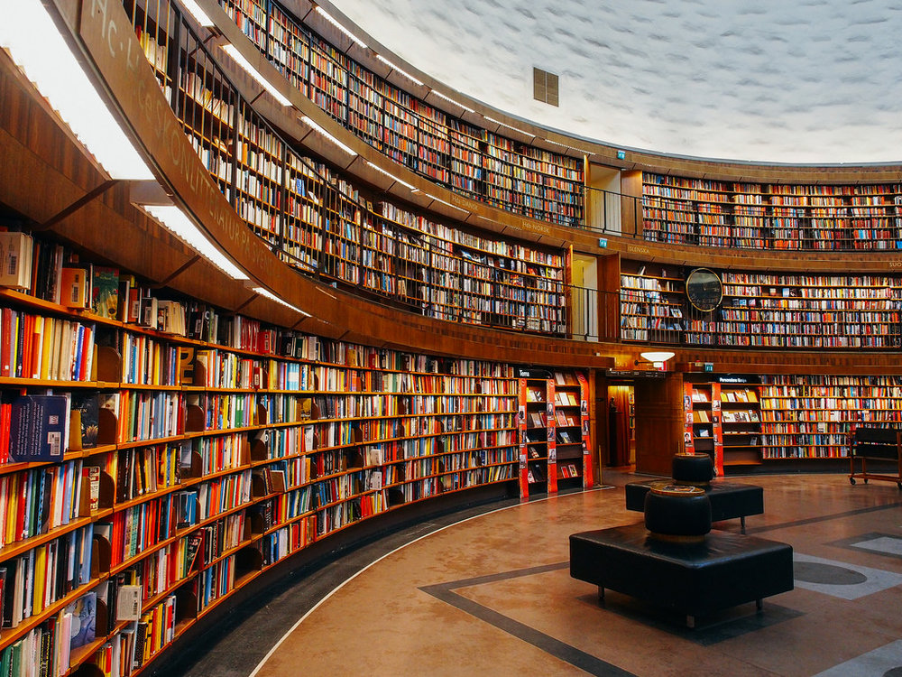 An image of a library. Hundreds of books on bookshelves appear in the image. Photo credit:  square(tea) on flickr