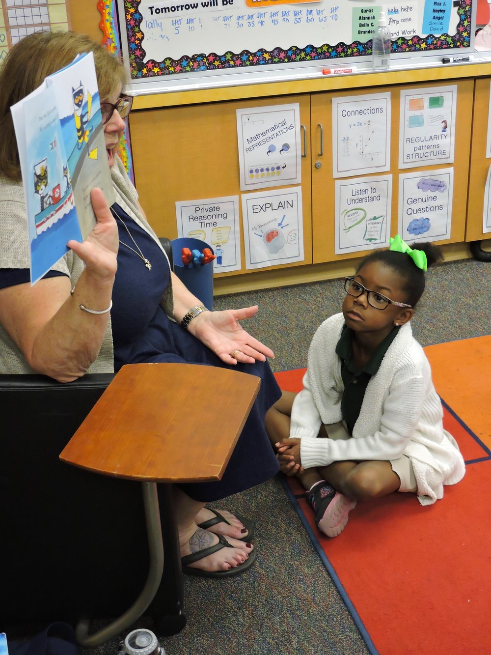 A picture of a young student paying rapt attention to a volunteer as they read a book aloud.