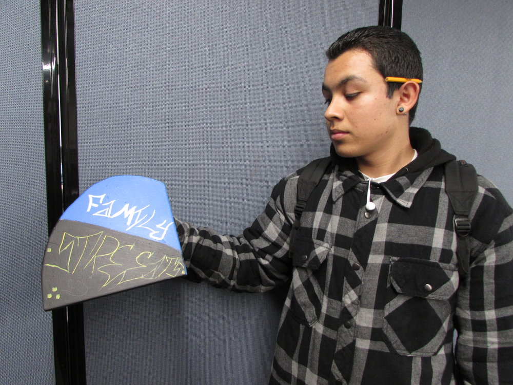 "An image of a student from 37ECB holding his piece of the communal sculpture. His piece was based around the theme, ""bravery."""