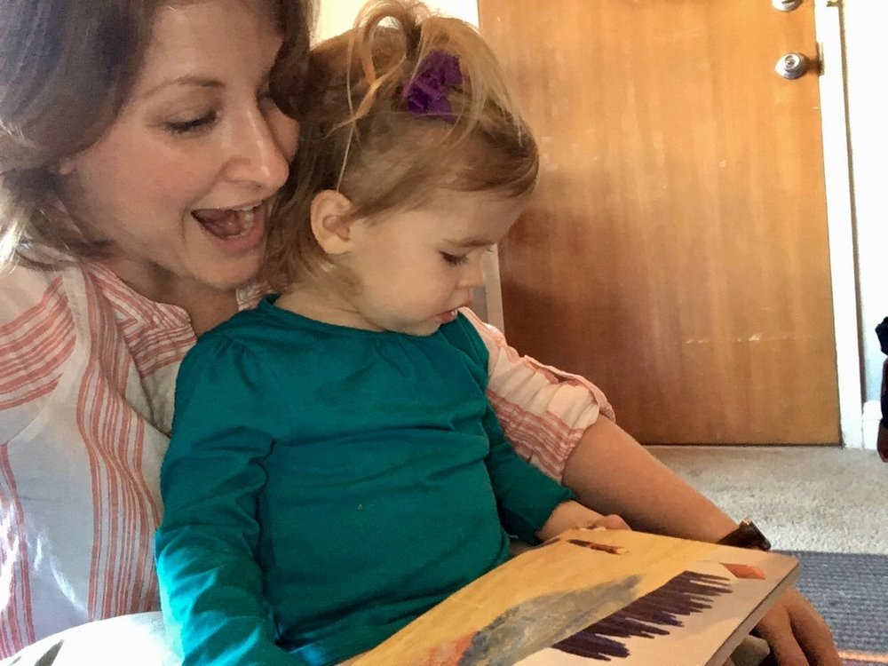 A picture of our Program Director, Amanda Birmingham Bonds, getting caught reading with her daughter!