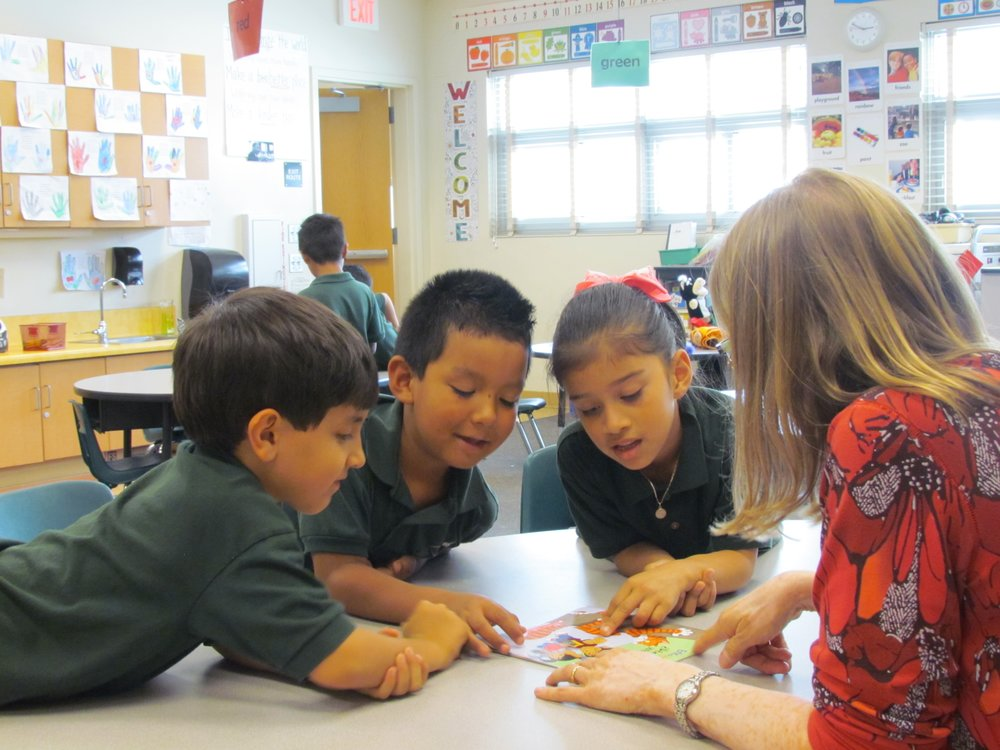 A picture of Read Aloud volunteer, Barb Takahashi, talking with Golden Hill students in her small group session.