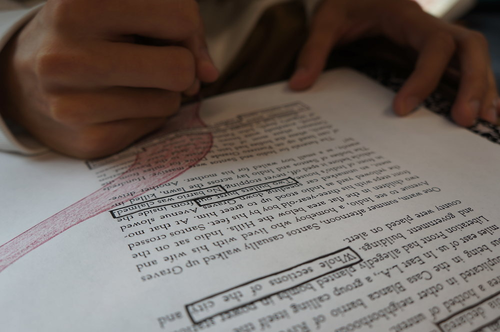 An image of one of our students from 37ECB working on a black out poem. The image features a page of a book and the student's hand.