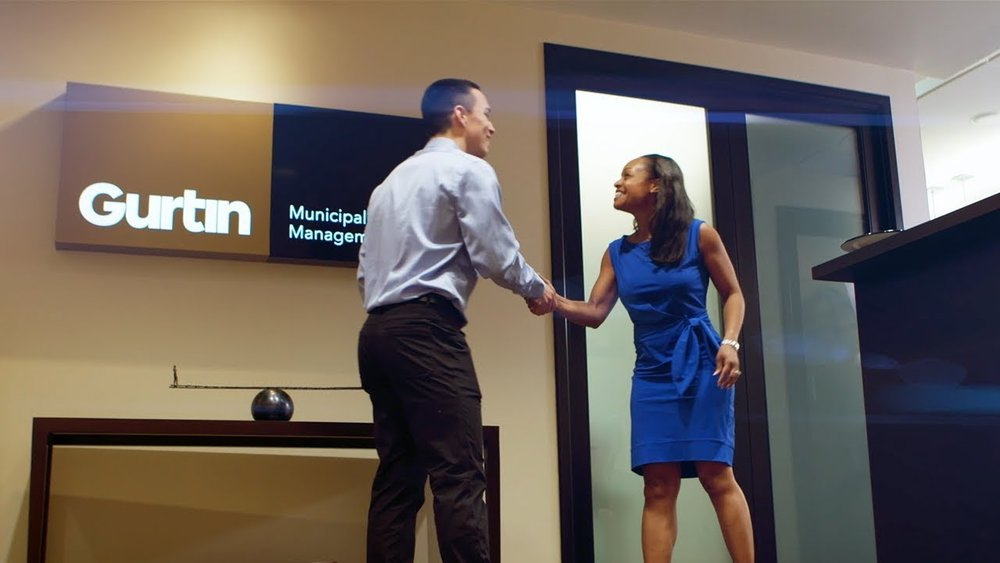 An image of two people shaking hands in the Gurtin Munucipal Bond Management offices.
