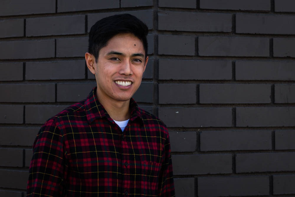 An image of John Camitan standing in front of a brick wall and smiling at the camera.