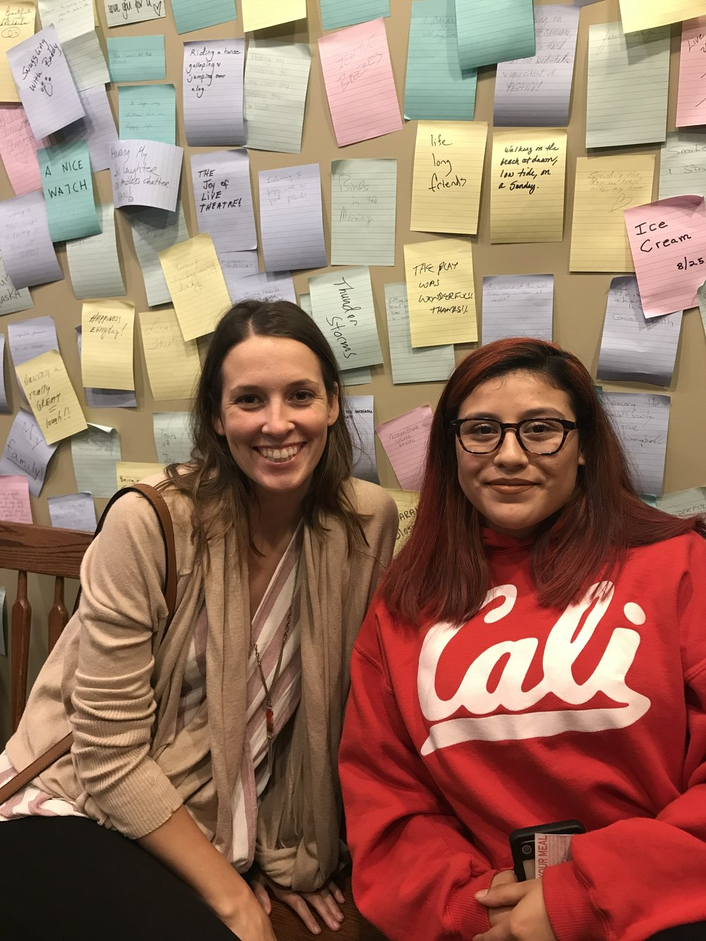 An image of scholar Alicia with her mentor, Keri. They are sitting in front of a wall full of posit-it notes.