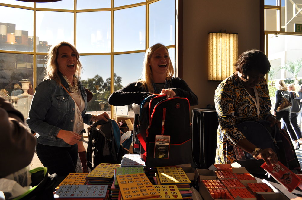 An image of three attendees of the Women's Day Event stuffing Kindergarten Readiness Backpacks.