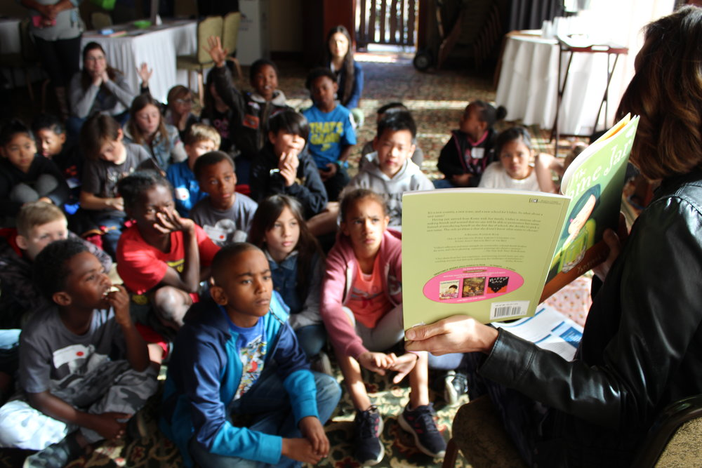 An image from our Champions for Youth Read Aloud event. A group of students stare intently at a book that is being help open by a member of the PGA Wives Association.