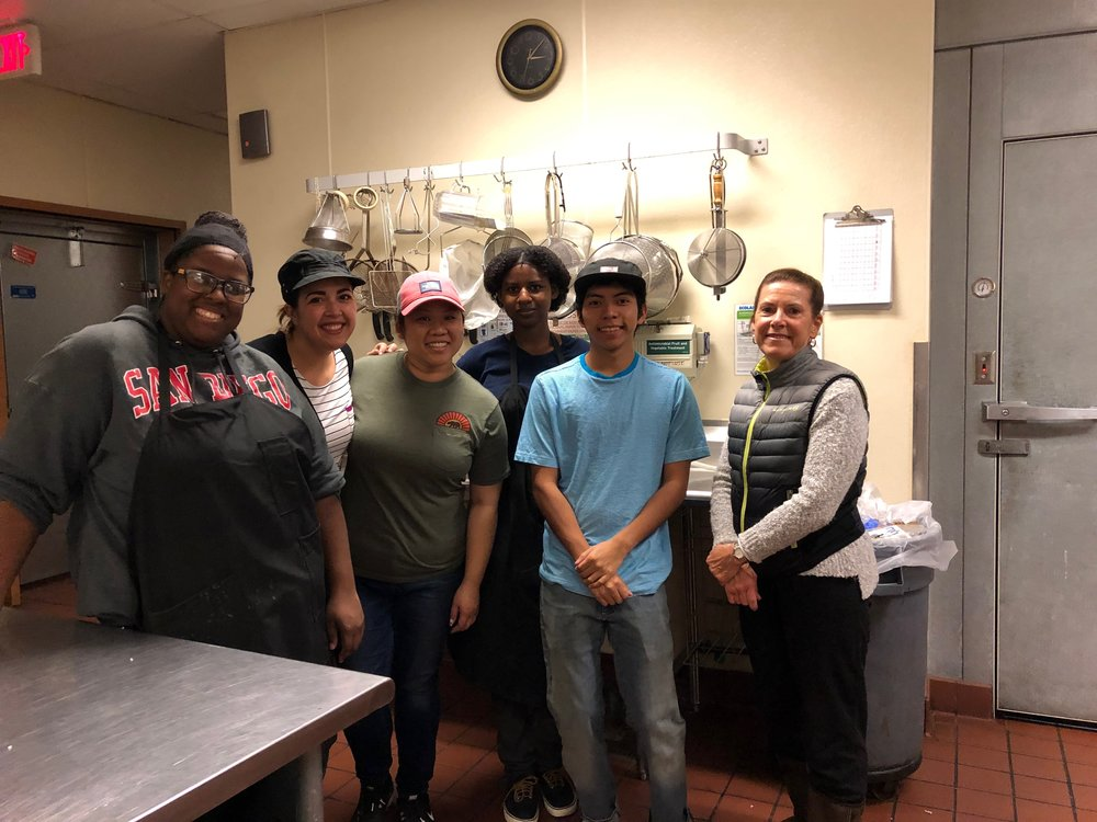 An image of our scholarship students and mentors at a volunteer day at Kitchens for Good.