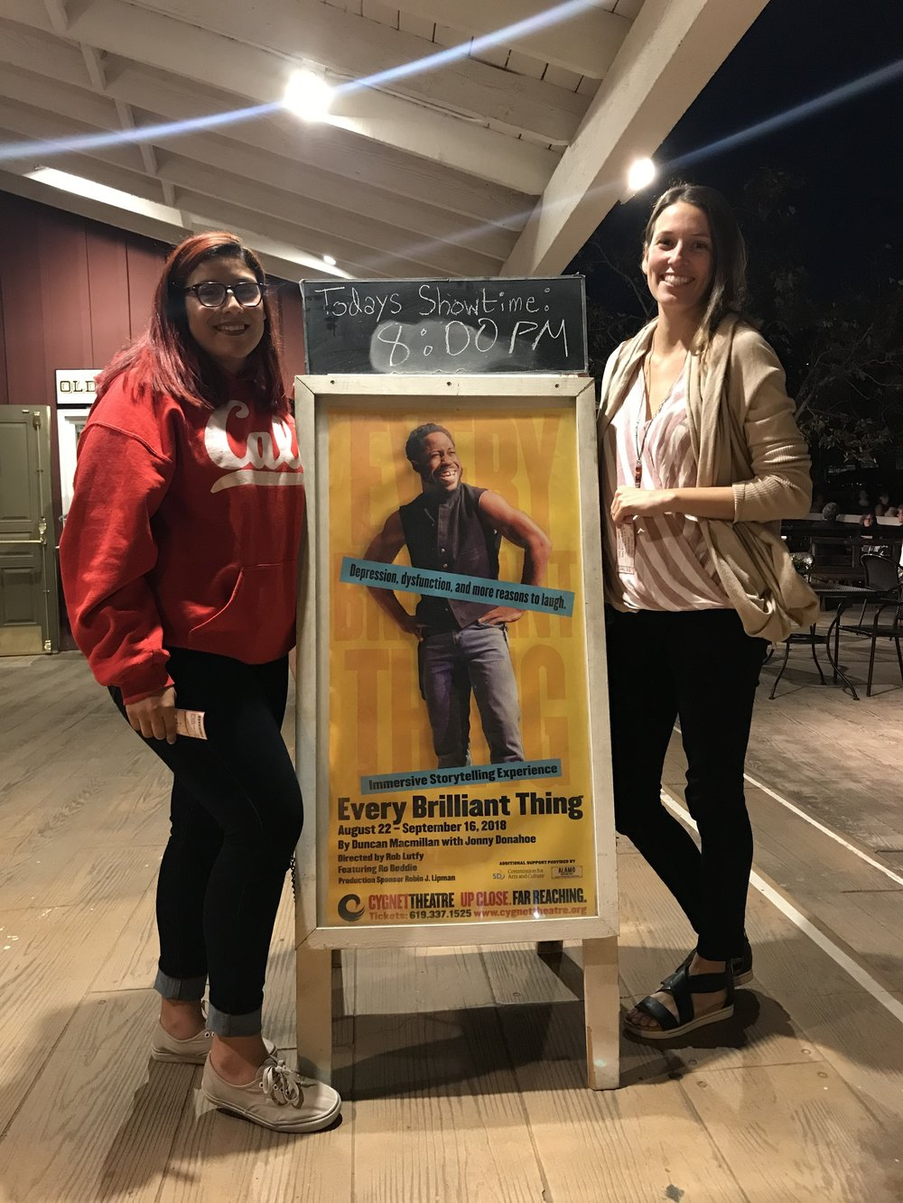 An image of Alicia and her mentor Kerrie standing in front of a sign for Every Brilliant Thing, a play that they went to see together.