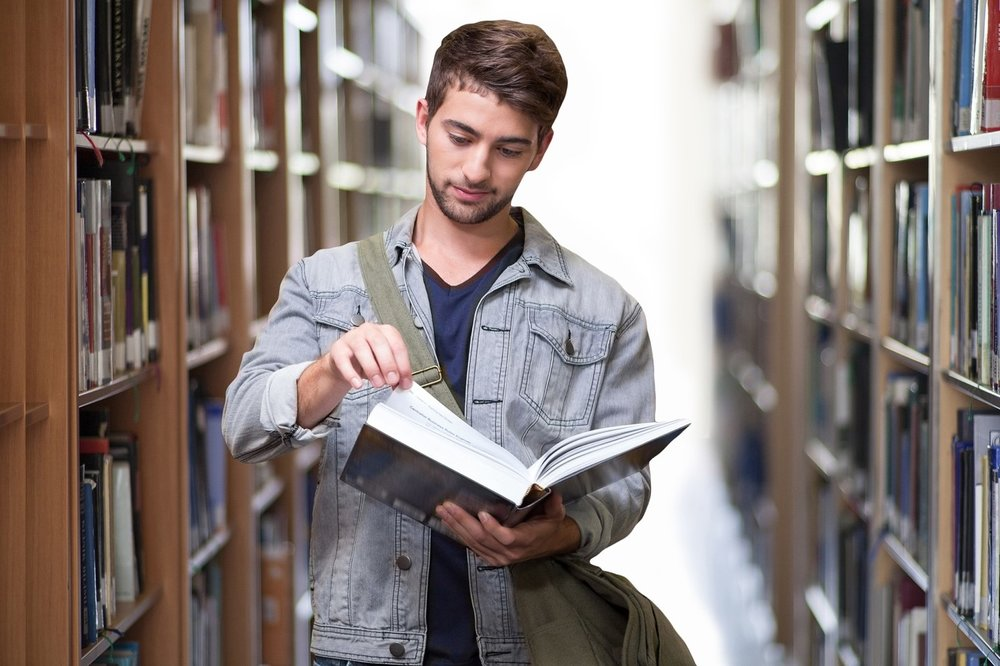 Image of a person standing in the middle of a library aisle, looking at a book that they are holding open.