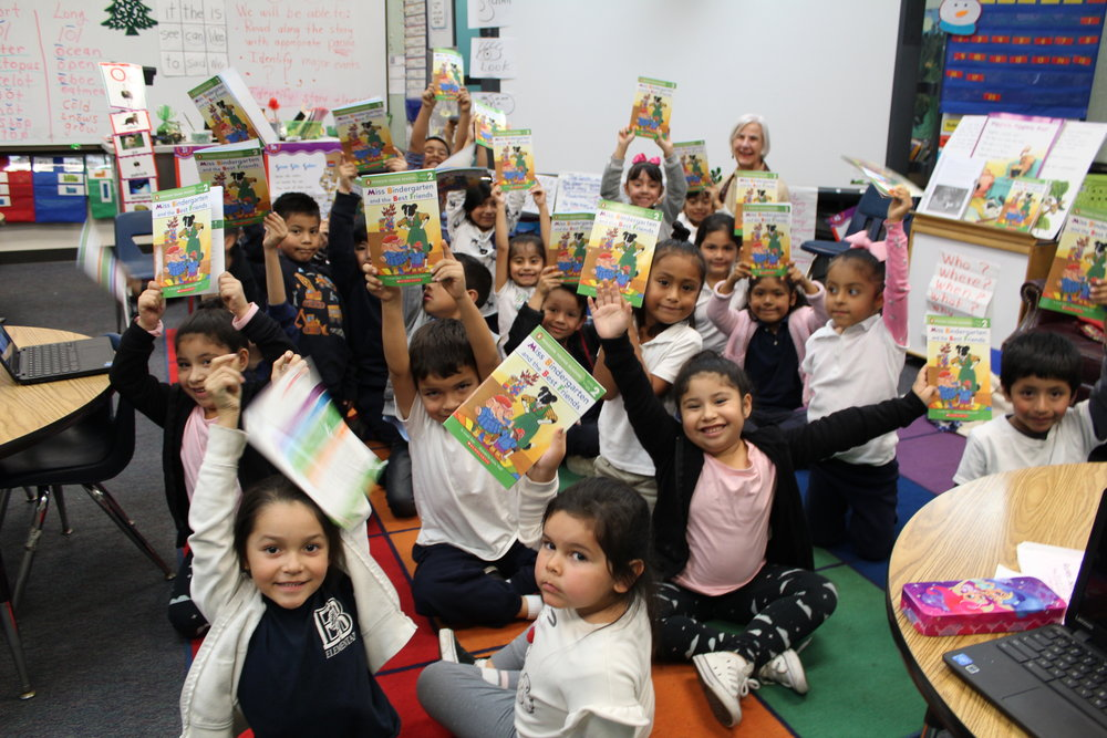 An image of a group of students in our Read Aloud Program excitedly holding up their books.