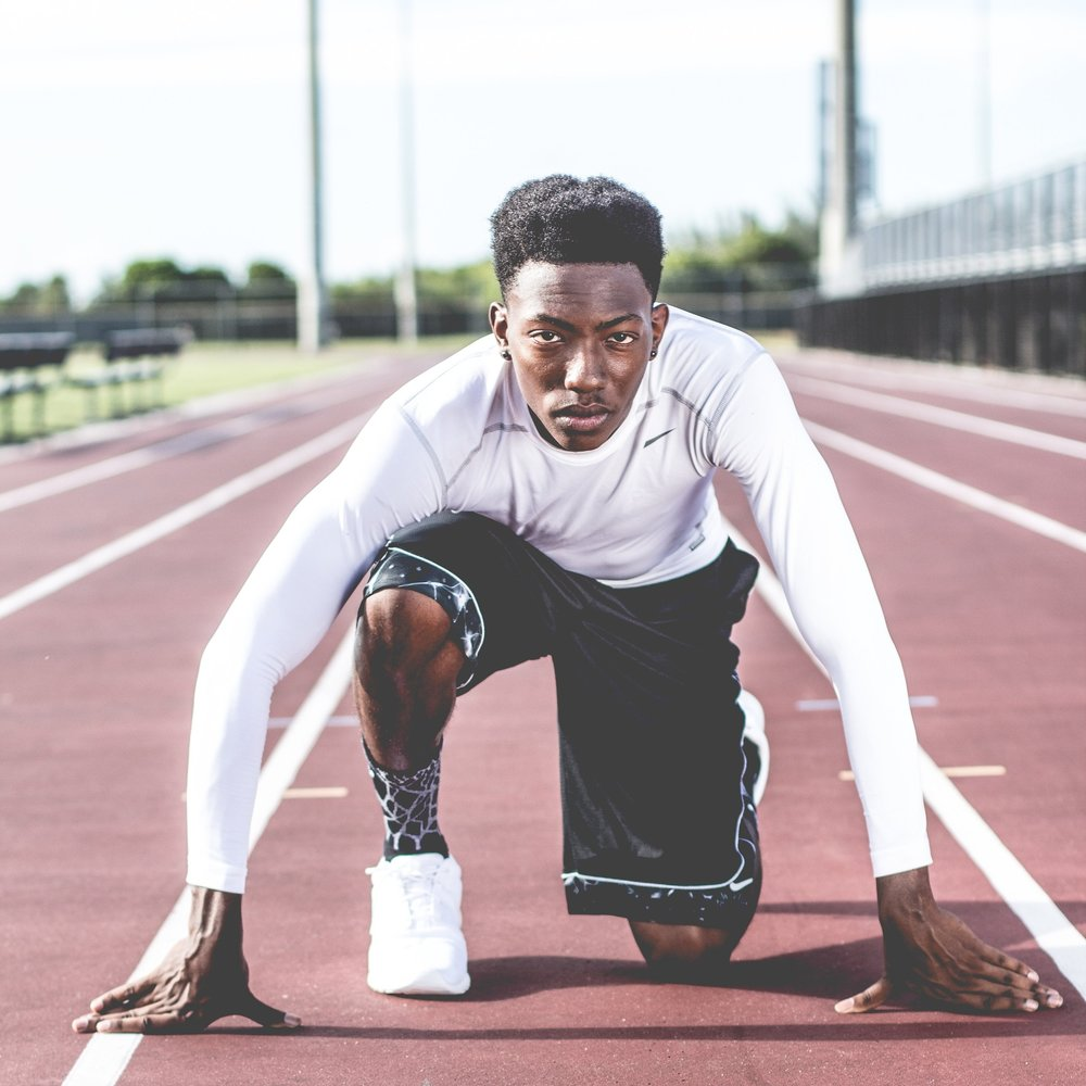 This image of an African-American man preparing to launch off the line on a running track should be emblematic of the motivation to excel. Where do you think that look of determination comes from?  Photo by  William Stitt on  Unsplash