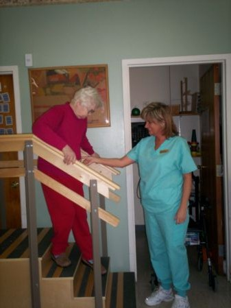 This picture shows one of our residents working on climbing stairs with a member of our rehab team.