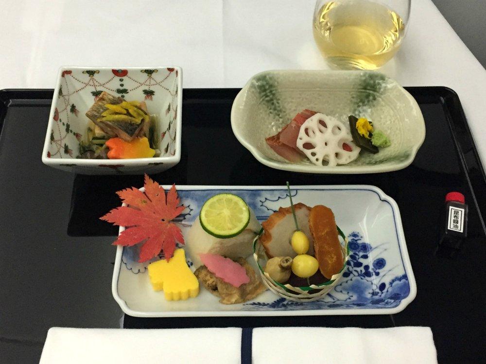 """Väliruoka; Zensai (Grillattu makrillisushi pyöriteltynä daikon retiisiin, haudutettua ginkgo-pähkinöitä suolaisessa kastikkeessa tarjoiltuna männyn neulasesta, paitettua vesikastanjaa, grillattu """"lentävä kala"""" kalakakku, uppopaistettua sailfin sandfish -kalaa vinegrette -kastikkeessa), Nimono (Höyrytettyä paksua tofua, isoja ituja ja shimeji sientä), Otsukuri (Sashimi: Merilevään kiedottua alfonsino -kalaa)"""