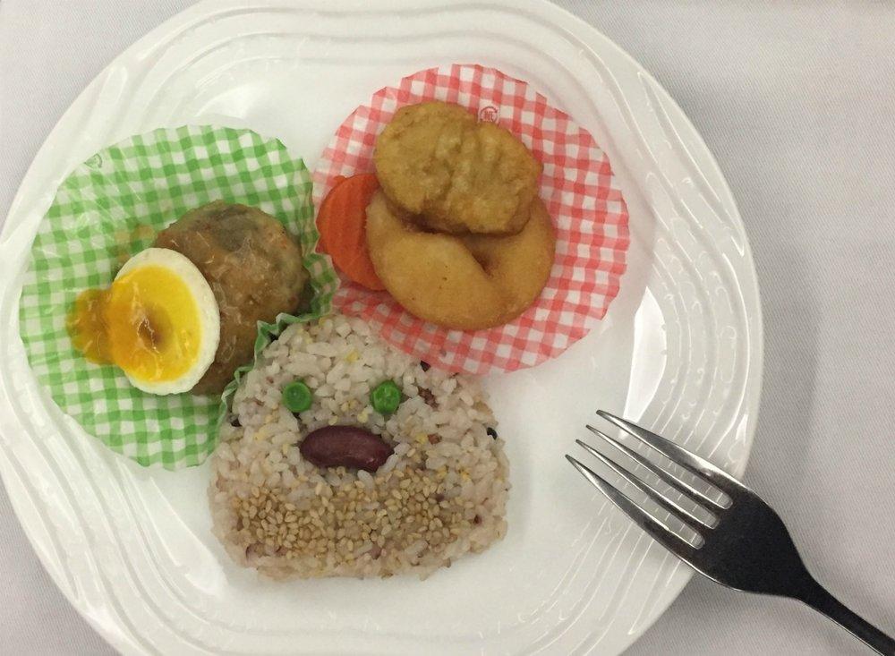 Lapsen alkuruokalautasella oli kananmunasta tehty kala ja karkkipaperiin käärittyä juustoa. Pääruokana oli kanaa ja riisiä.