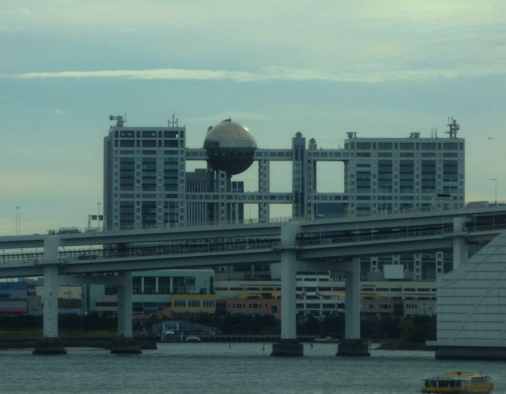 Tämä arkkitehtuurisesti erikoisen rakennuksen voi nähdä ainakin junasta matkalla Odaibaan. Se on Fuji Television päämaja jonka sisälle pääsee myös vierailulle.