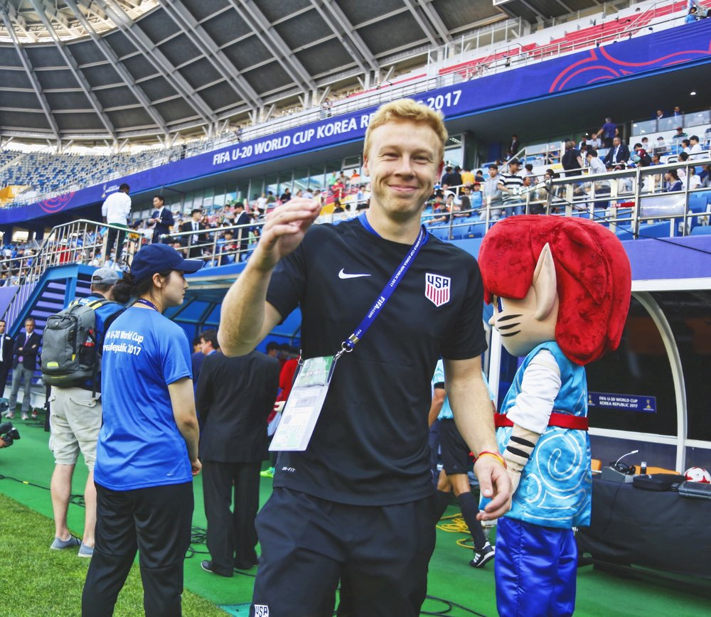 Daejeon, South Korea - Bobby daps up his buddy Logan, the team's content videographer, before taking his seat on the bench for the final group stage match against Saudi Arabia.