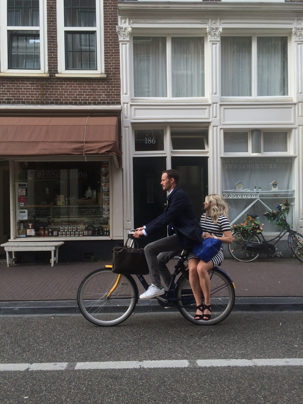"A couple ""dinking"" on an OV fiets bike share bicycle.  These bike share bicycles are located at train stations to allow those who arrive by train to get to their destination."