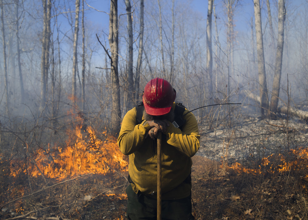 Jason Bew, the engine captain at the Wayne National Forest service, takes a momentary break late in the day of a prescribed burn on Friday, March 17, 2017.