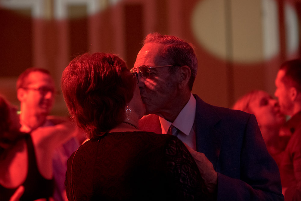 A couple kisses on the dance floor.