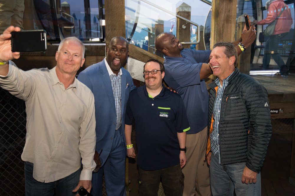 Kenny mayne, gary payton, trent marshall (athlete), ray roberts, and steve largent ham it up for selfies by the great wheel.