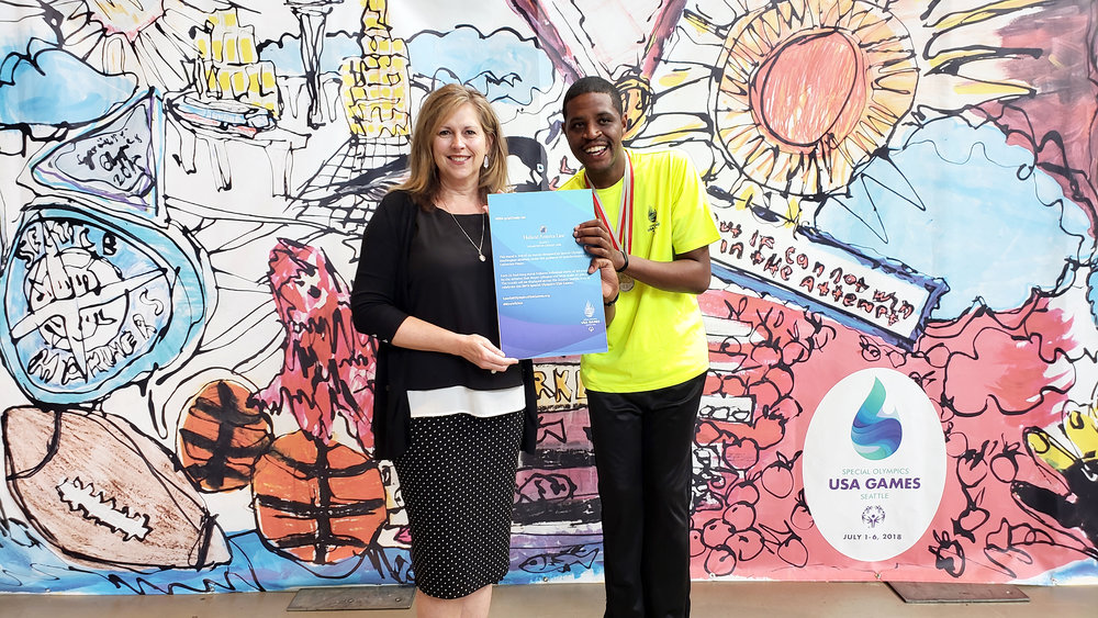 Sally Andrews, VP of Public Relations for Holland America Line and Special Olympics athlete, Frankie Hogan at the unveiling of one of the murals at the Seattle Center Armory.