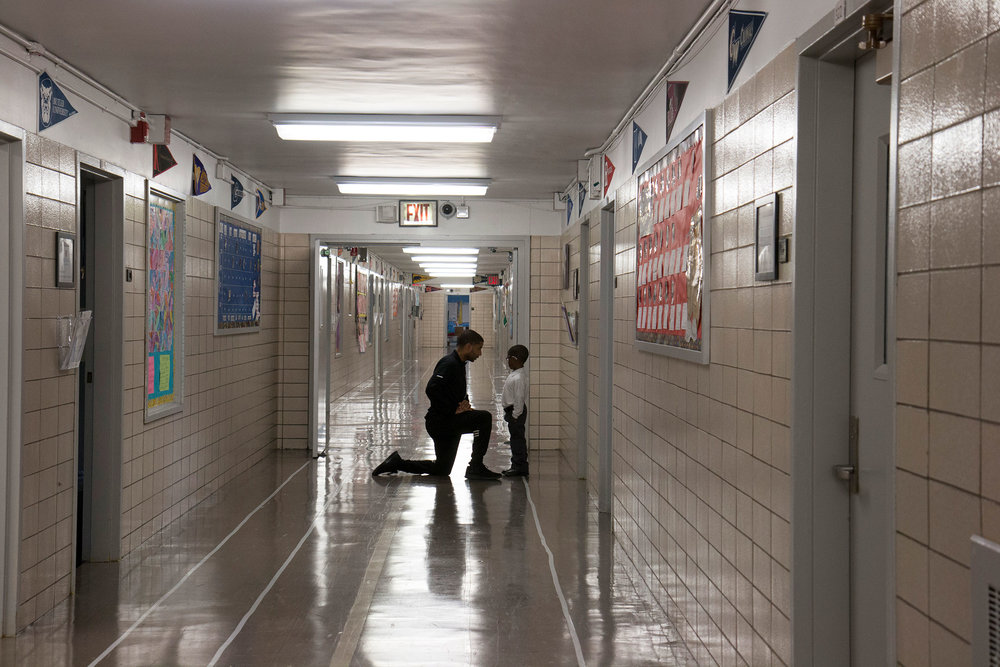 Gibran Jordain-Earl, a fitness teacher and coordinator of the community involvement program at Leadership Prep Canarsie, talks to a student in the hall.