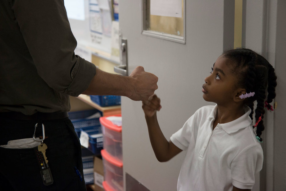 Second grader, Nalanie, fist bumps with her teacher, Kevin Grijalva.
