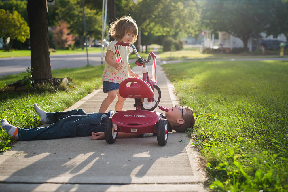 """A """"tragic accident"""" on our front sidewalk one day. In reality, The Boy put the bike on him and made it appear as if she'd run over him. Pretty ingenious in this mama's humble opinion. She's full of sass and he's full of drama and craziness."""