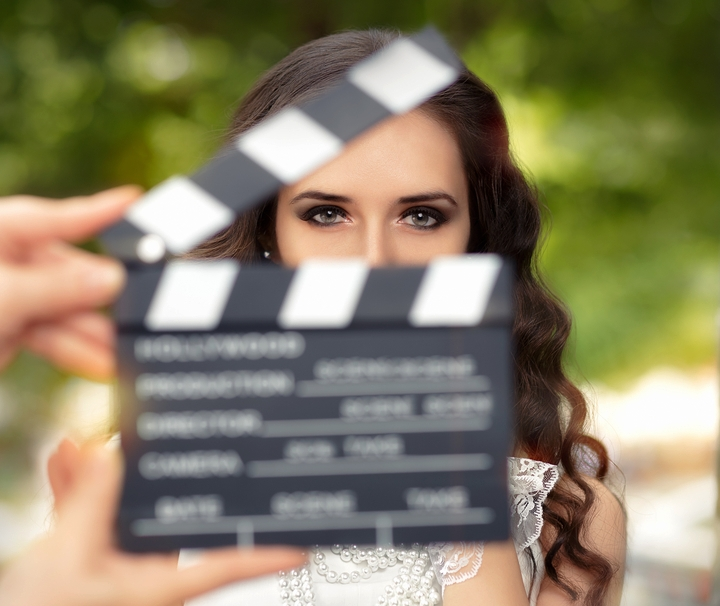 young woman looks at the camera through an open movie slate