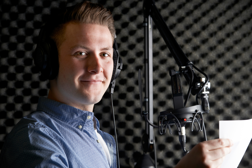 man smiles at the camera with a studio microphone in front of him.