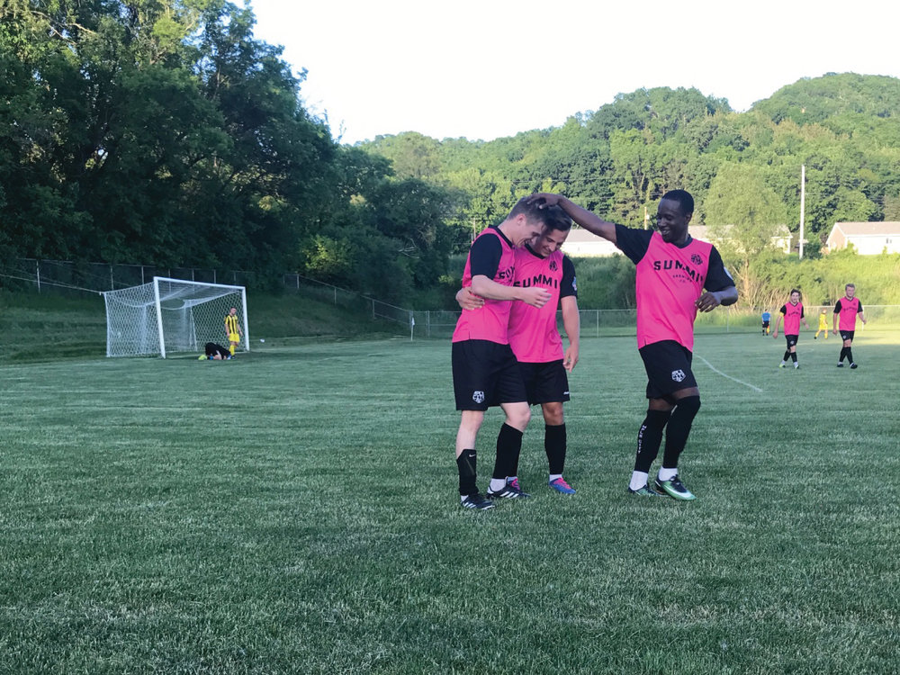 Ian Smith celebrates his goal against La Crosse Aris with Isaac Friendt and Whitney Browne