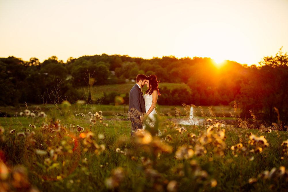 A wedding couple posing in a field