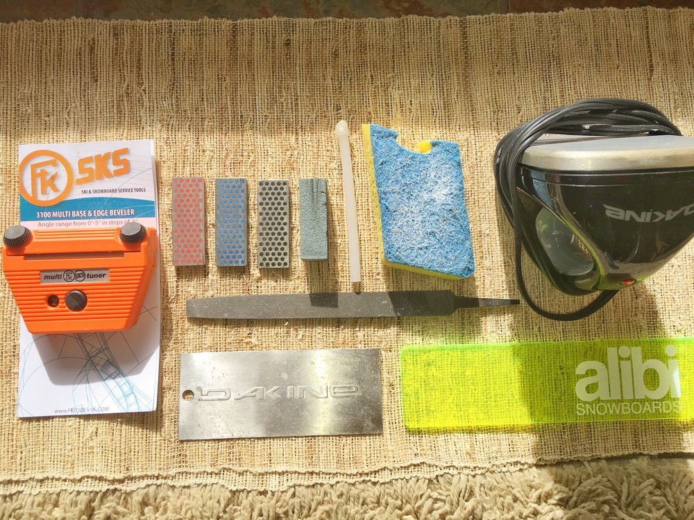 Top left to right: tuning side/base edge tool with file inserted, diamond stones (fine, medium, course), gummy stone, p-tex stick, nylon scourer, waxing iron. Middle: medium-cut file. Bottom left to right: metal scraper, plastic scraper.
