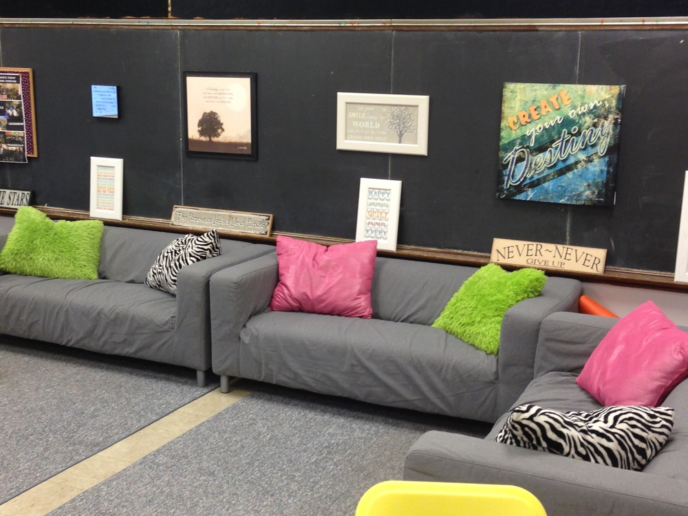 I have never regretted moving away from traditional seating. I love how the couches make it feel cozy and comfortable. We can have real discussions about books. A bonus that has occurred: improved classroom management. When students are comfortable, as with most people, they are more likely to stay on task and want to learn.  Also, since my school is 150 years old, chalkboards cover three sides of my room. I HATE chalkboards. I try to cover most of them with inspirational quotes or fabric. (I'm known as the quote lover now. My family and friends get them for me as gifts.) A lot of the sayings encourage a growth mindset.