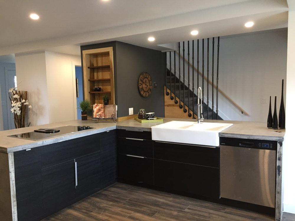 The Counters are Concrete, Farmhouse sink, Stainless taps and appliances, Pipe Wall Accents.