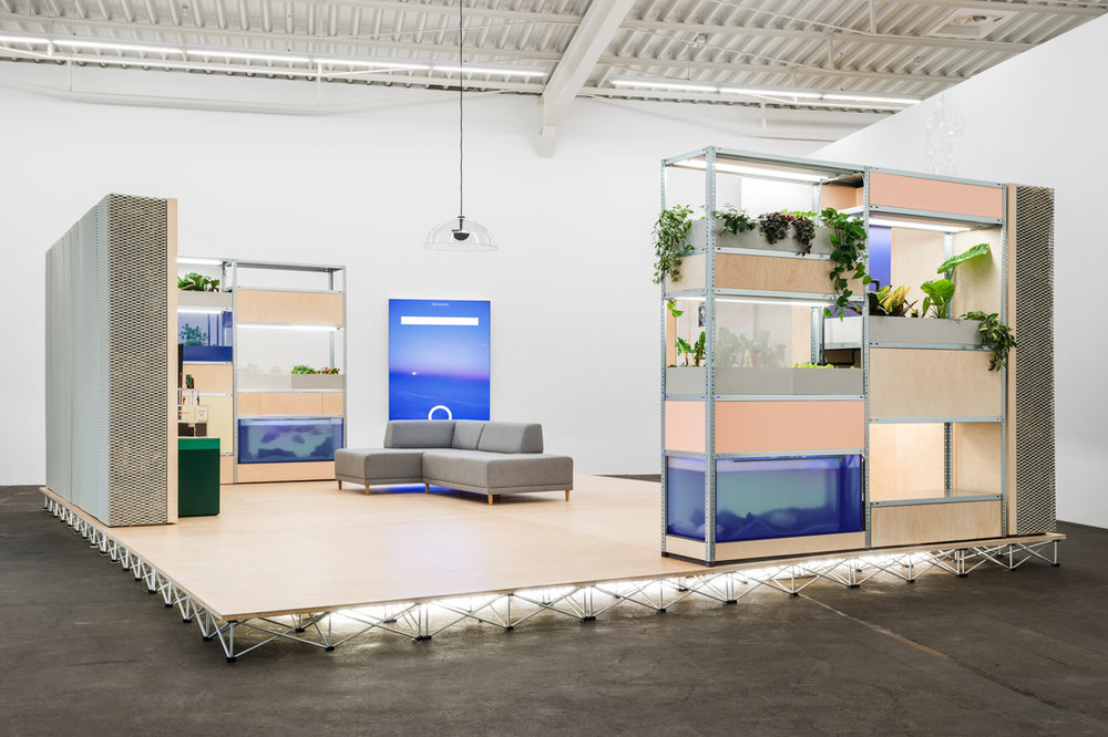 Installation view, 'moving is in every direction. Environments - Installations - Narrative Spaces', curated by Anna-Catharina Gebbers and Gabriele Knapstein, Hamburger Bahnhof - Museum für Gegenwart, Berlin  Christopher Kulendran Thomas, New Eelam, 2017 in collaboration with Annika Kuhlmann  Experience suite with aquaponic farming system, straw bale walls, lightboxes, VR model and HD video, 30 min: 60 million Americans can't be wrong in collaboration with The Mycological Twist, featuring works by Juliette Bonneviot, Muvindu Binoy, Simon Denny and Mirak Jamal   © Nationalgalerie im Hamburger Bahnhof, SMB / Photo: Jan Windszus