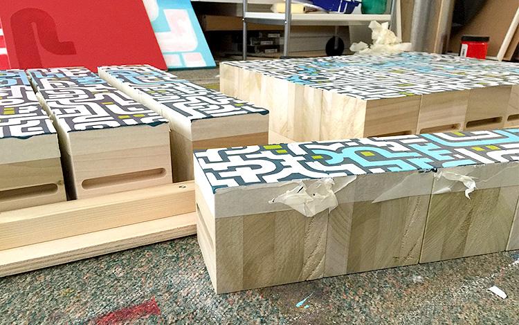 Removing the masking tape on the wooden painted blocks - Artwork Dutch contemporary artist Mr. Upside Michiel Nagtegaal painting KPN Teamdag 2016 give-away gift kunst cadeau in Mr. Upside Studio