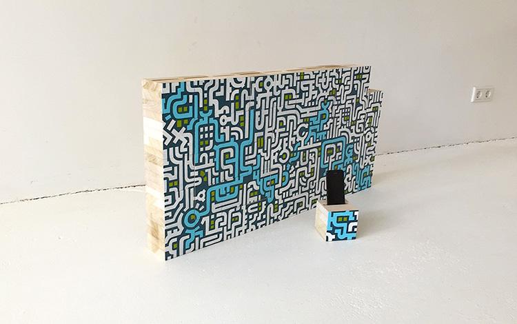 Complete wall of wooden blocks with Separate wooden block with cell phone in slot - Mr. Upside Gallery Voorburg - Artwork Dutch contemporary artist Mr. Upside Michiel Nagtegaal painting KPN Teamdag 2016 give-away gift kunst cadeau in Mr. Upside Studio