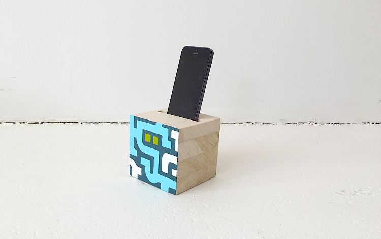 Photo 3 of wooden phone holders, a commissioned artwork by KPN, a large Dutch telecommunications provider. Phone holders are painted on one side. Artwork created by Dutch contemporary urban artist Michiel Nagtegaal / Mr. Upside.