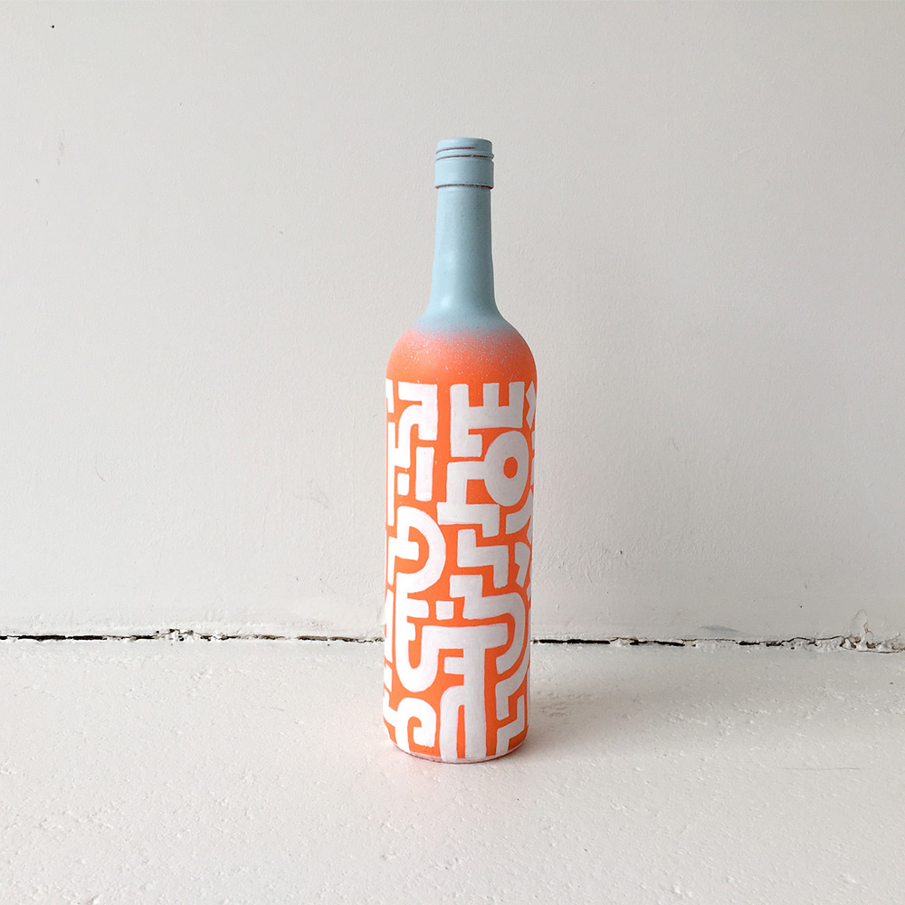 Photo 2 of Art Bottle 'Bright Orange with Light Blue and White'. The art object is a painted wine bottle by Dutch contemporary urban artist Michiel Nagtegaal / Mr. Upside.