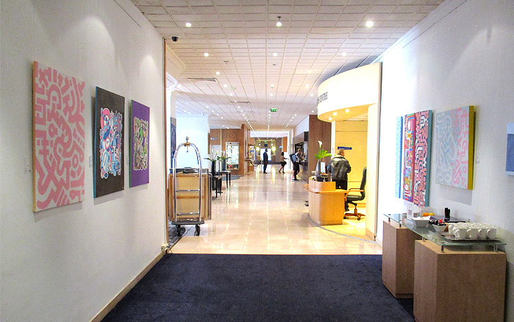 Mr. Upside Art on view in the Hilton Orly Airport Hotel in Paris, France - Full view of the hallway which leads to the hotel lobby with seven paintings on the wall