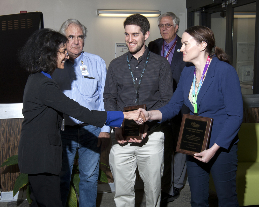 US DOE Fuel Cell Technologies Office Director Sunita Satyapal shakes hands with Katrina Groth and Ethan Hecht, award recipients, while Jay Keller and Art Pontau look on. (photo credit: Randy Wong)