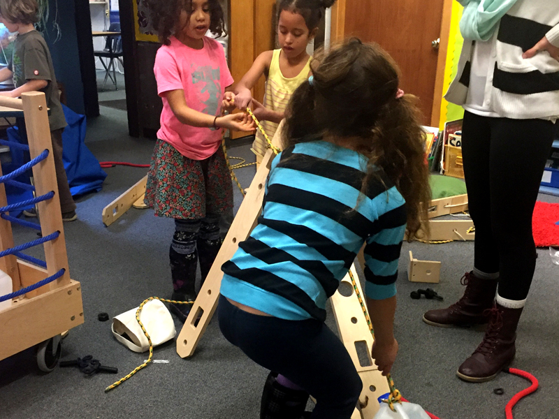 Students collaboratively pull jug up ramp