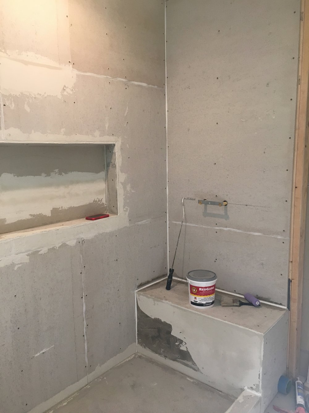 A view inside the shower showing the large shower niche and bench as backer board is going in before the tile.