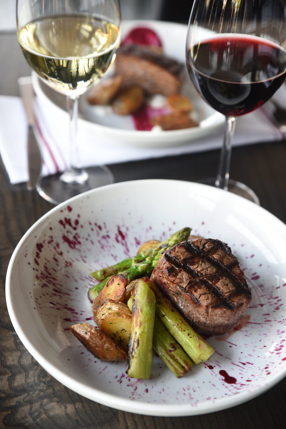 Filet Mignon with herb roasted fingerling potatoes, grilled asparagus & a red beet, port reduction.