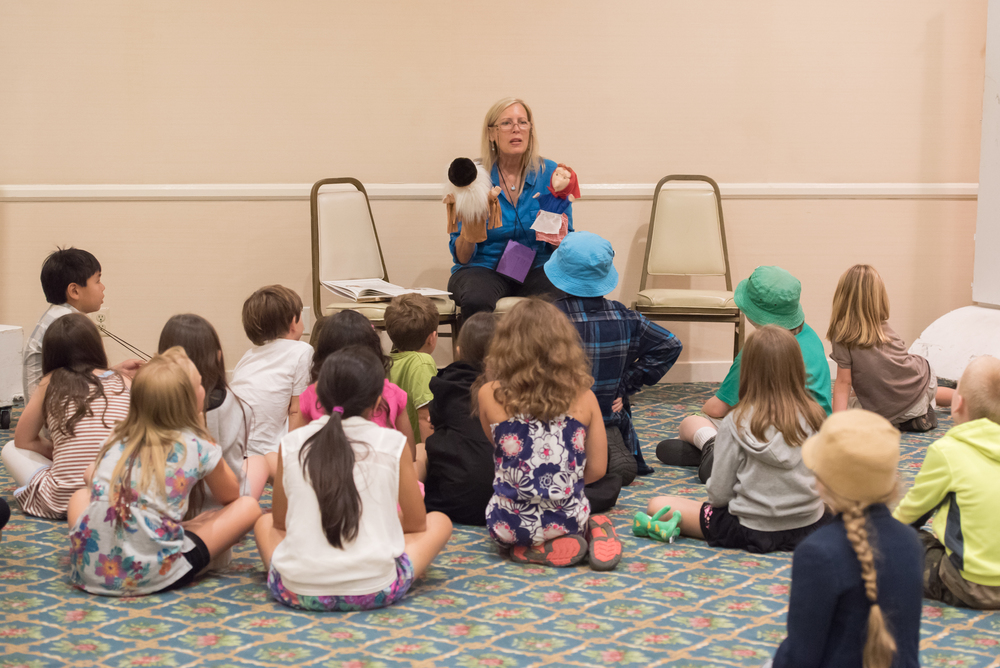 "Storyteller, Dr. Jenelle Miller, performing the   Tajar Tales   with puppets during a break between children's sessions at the National MENSA Conference 2016. Dr. Miller and her artist sister, Jill Kerry, republished this whimsical tale written by Jane Shaw Ward in the 1920s, and then created the puppets, plush Tajar dolls, and an audio CD to develop a complete ""story kit."" Dr. Miller uses the story kit in her ""Student Publisher's Workshop"" where she teaches children how to collaborate together to write, illustrate, and narrate stories as well as make puppets and perform puppet shows. See  Tajar's Classic Works  and  Accelerated Academics Puppetry"