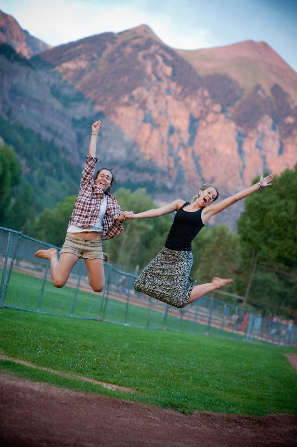 two volunteers jump for joy in the mountains