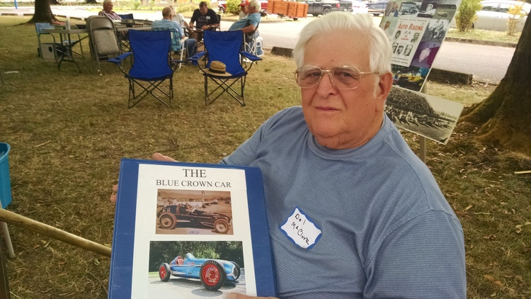 Del McClure holding book covering history of the Blue Crown