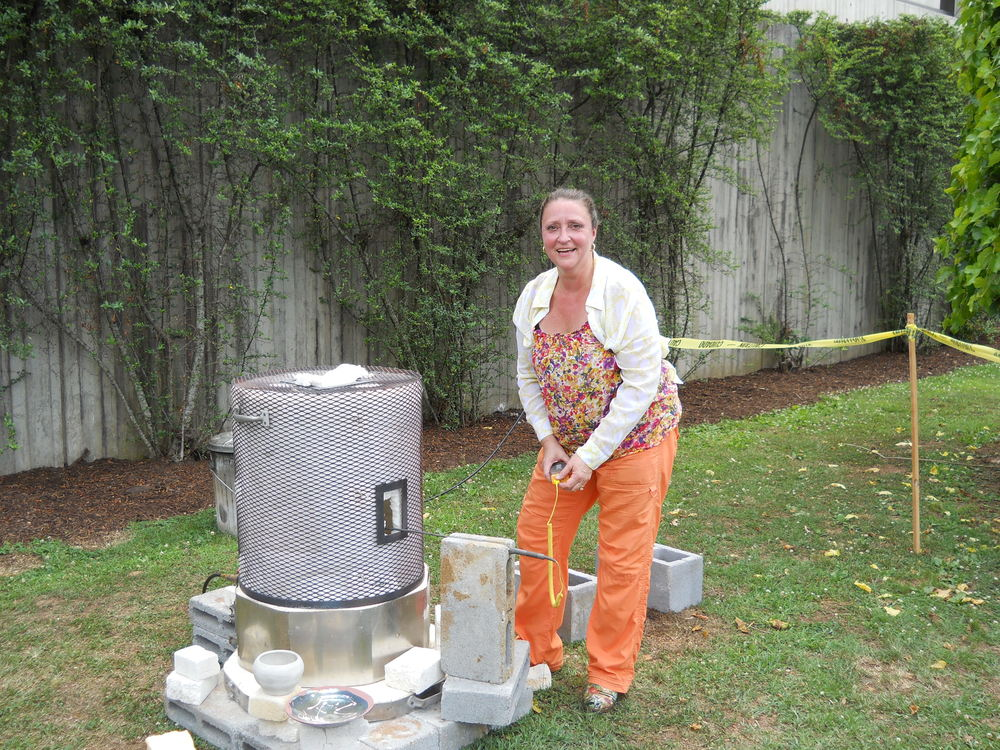 """Linda Mabry will be demonstrating raku firing in front of the bus and shuttle drop-off area during the festival until 4 pm each day. This ancient process, while seeming almost magical, is a study in the properties of physics as one pulls a white-hot piece from the flame and places it in combustible material to smoke. Come watch Linda """"burn"""" with unbridled passion."""
